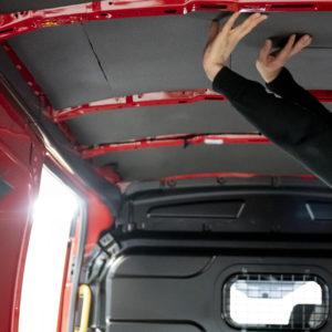 Montör sätter isolering i transportbilstak.