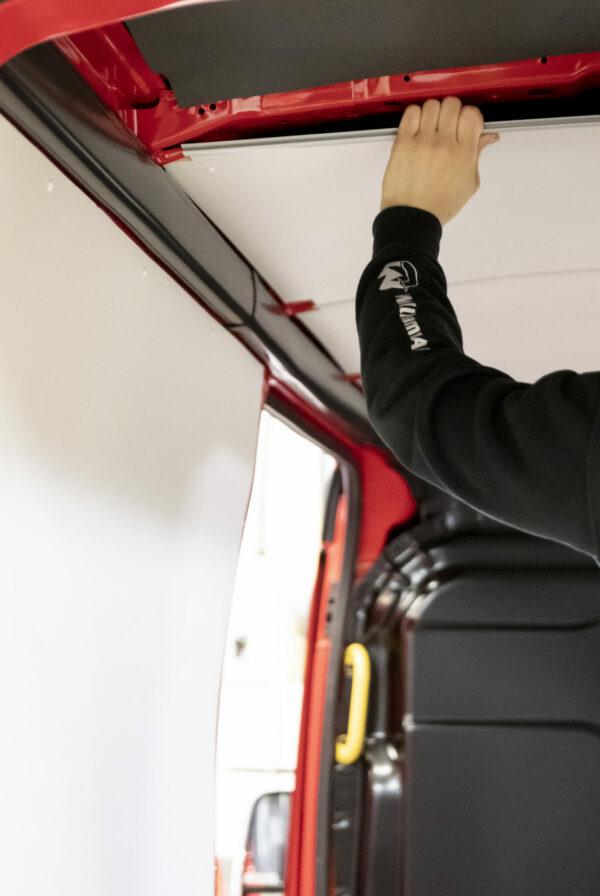 Montör monterar vit inklädnad i tak